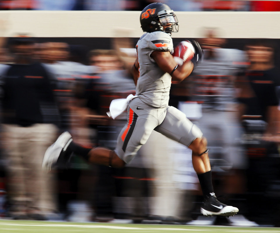 Photo - Oklahoma State's Justin Gilbert (4) returns a kickoff for a touchdown in the first quarter during a college football game between Oklahoma State University (OSU) and West Virginia University (WVU) at Boone Pickens Stadium in Stillwater, Okla., Saturday, Nov. 10, 2012. Photo by Nate Billings, The Oklahoman
