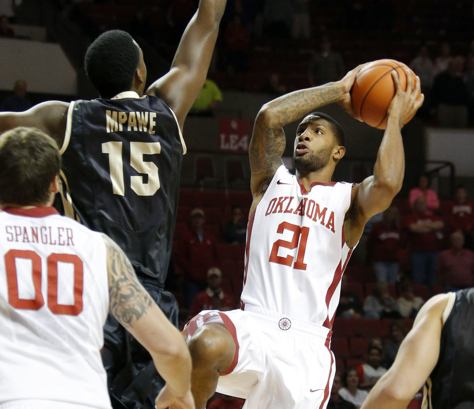 Photo - Oklahoma's Cameron Clark (21) goes to the basket beside Idaho's Paulin Mpawe (15) during a college basketball game between the University of Oklahoma Sooners and the Idaho Vandals at Lloyd Noble Center in Norman, Okla., on Wednesday, Nov. 13, 2013. Wednesday, Nov. 13, 2013. Photo by Bryan Terry, The Oklahoman