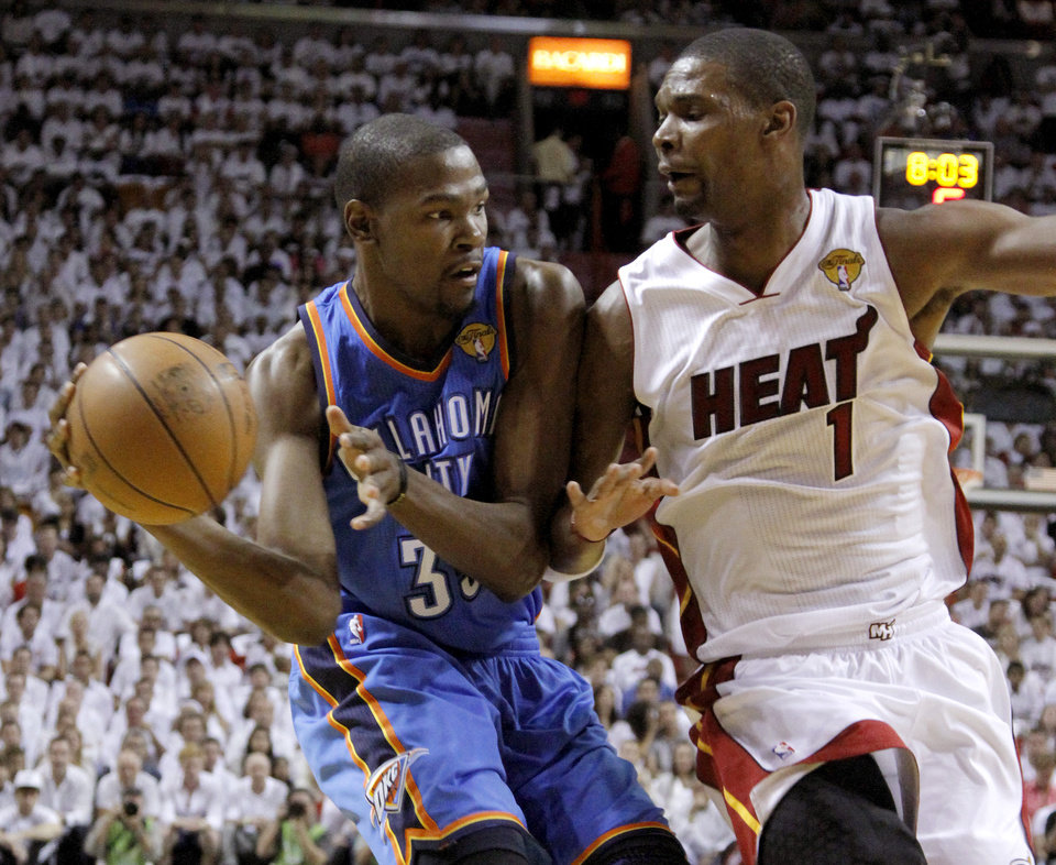 Photo - Oklahoma City's Kevin Durant (35) looks to pass around Miami's Chris Bosh (1) during Game 3 of the NBA Finals between the Oklahoma City Thunder and the Miami Heat at American Airlines Arena, Sunday, June 17, 2012. Photo by Bryan Terry, The Oklahoman