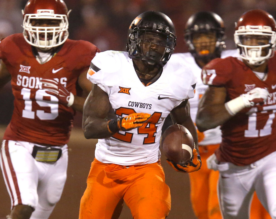Photo - Oklahoma State's Tyreek Hill (24) returns a punt for a touchdown as Oklahoma's Wesley Horky (42), Eric Striker (19) and Jordan Smallwood (17) try to catch him during the Bedlam college football game between the University of Oklahoma Sooners (OU) and the Oklahoma State Cowboys (OSU) at Gaylord Family-Oklahoma Memorial Stadium in Norman, Okla., Saturday, Dec. 6, 2014. Photo by Sarah Phipps, The Oklahoman