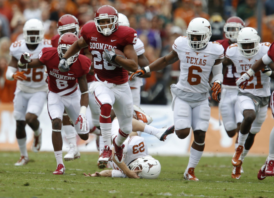 Photo - Oklahoma's Alex Ross (28) returns a kickoff for a touchdown during the Red River Showdown college football game between the University of Oklahoma Sooners (OU) and the University of Texas Longhorns (UT) at the Cotton Bowl in Dallas on Saturday, Oct. 11, 2014. 