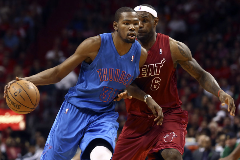 Photo - Oklahoma City Thunder's Kevin Durant (35) drives against Miami Heat's LeBron James during the second half of an NBA basketball game in Miami, Tuesday, Dec. 25, 2012. The Heat won 103-97. (AP Photo/J Pat Carter) ORG XMIT: FLJC114