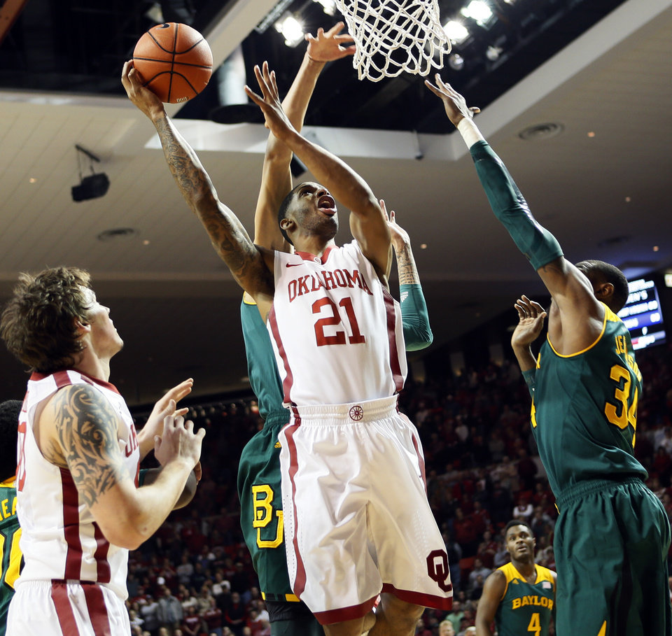 Photo - Oklahoma's Cameron Clark (21) takes the ball to the hoop in front of Baylor's Isaiah Austin (21) and next to Cory Jefferson (34), right, and Oklahoma's Ryan Spangler (00)  during an NCAA men's college basketball game between Baylor and the University of Oklahoma (OU) at Lloyd Noble Center in Norman, Okla., Saturday, Feb. 8, 2014. Photo by Nate Billings, The Oklahoman