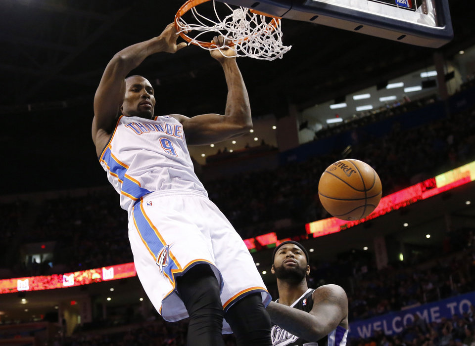 Photo - Oklahoma City Thunder forward Serge Ibaka (9) dunks in front of Sacramento Kings center DeMarcus Cousins (15) in the third quarter of an NBA basketball game in Oklahoma City, Sunday, Jan. 19, 2014. Oklahoma City won 108-93. (AP Photo/Sue Ogrocki)