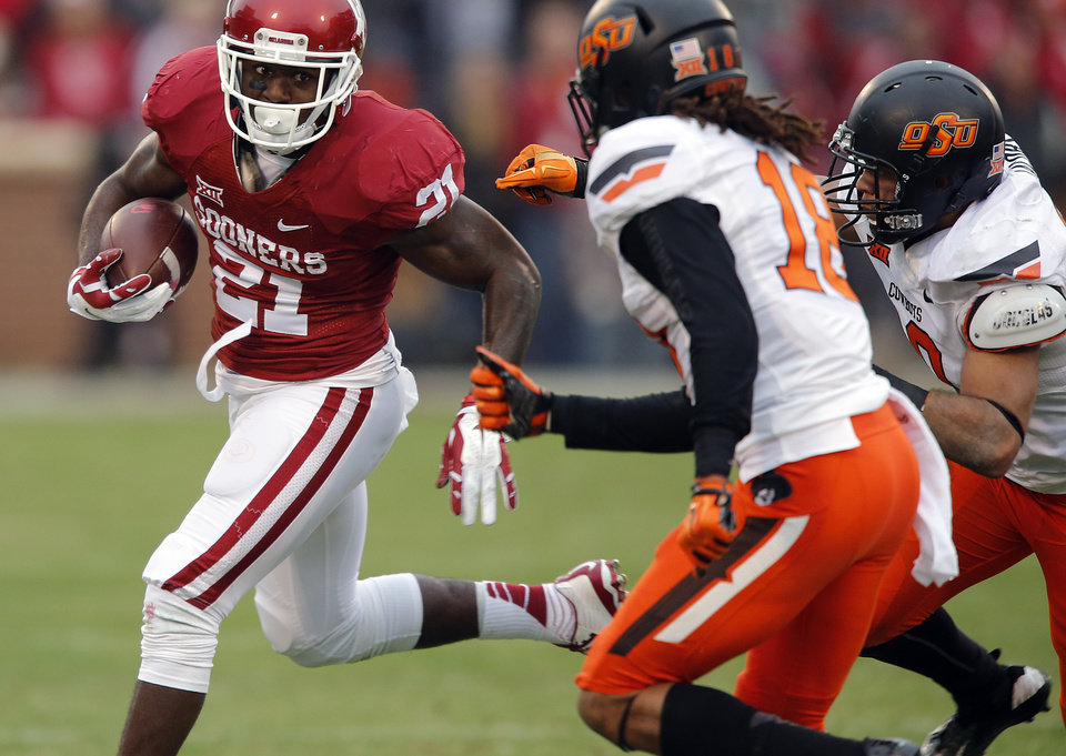 Photo - Oklahoma's Keith Ford (21) runs past Oklahoma State's Ramon Richards (18) during a Bedlam college football game between the University of Oklahoma Sooners (OU) and the Oklahoma State University Cowboys (OSU) at the Gaylord Family Oklahoma Memorial Stadium in Norman, Okla. on Saturday, Dec. 6, 2014. Photo by Chris Landsberger, The Oklahoman