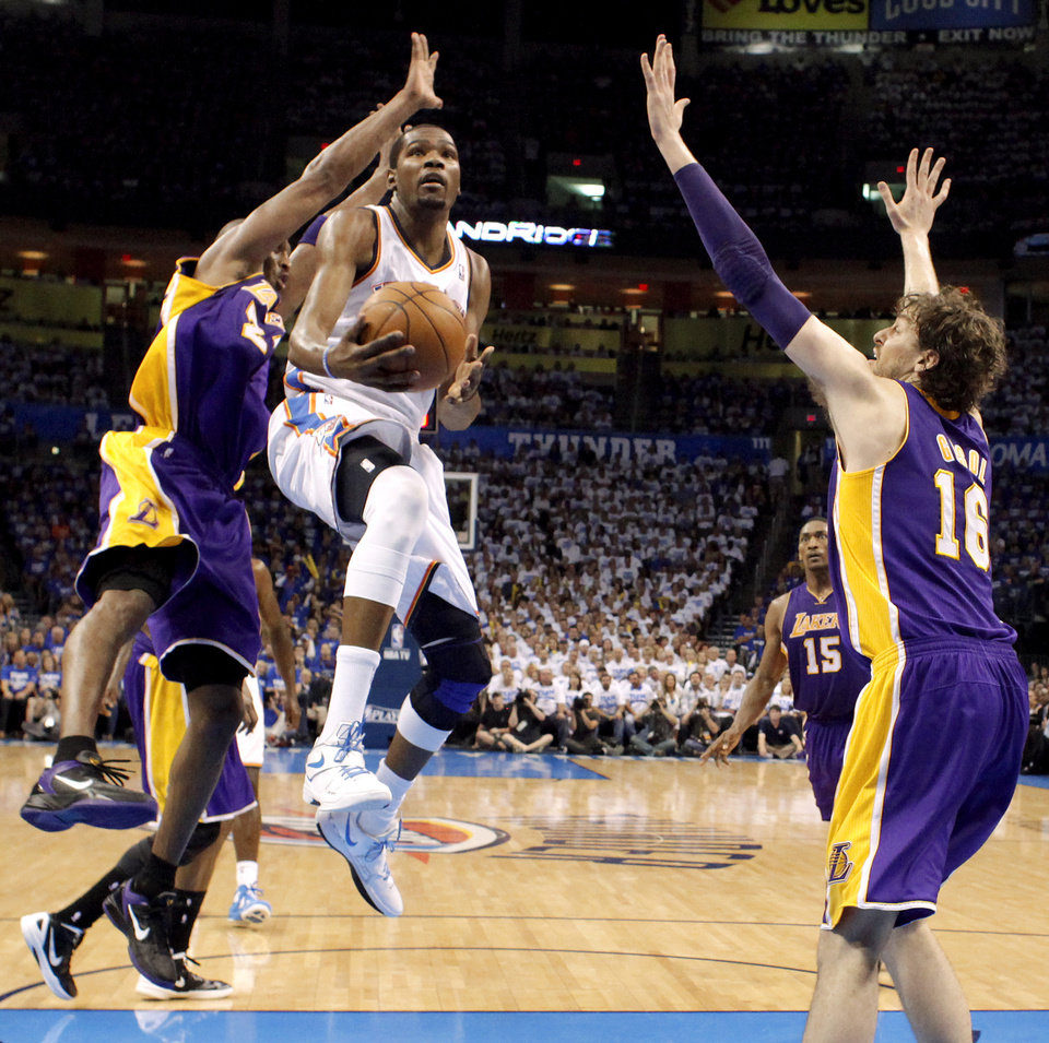 Photo - Oklahoma City's Russell Westbrook (0) goes to the basket between Los Angeles' Kobe Bryant (24) and Pau Gasol (16) during Game 2 in the second round of the NBA playoffs between the Oklahoma City Thunder and L.A. Lakers at Chesapeake Energy Arena in Oklahoma City, Wednesday, May 16, 2012.  Oklahoma City won 77-75. Photo by Bryan Terry, The Oklahoman