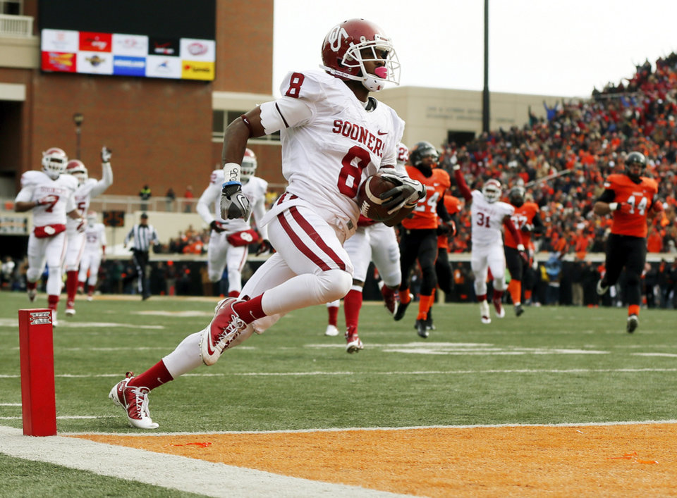 Photo - Oklahoma's Jalen Saunders (8) returns a punt for a touchdown in the first quarter during the Bedlam college football game between the Oklahoma State University Cowboys (OSU) and the University of Oklahoma Sooners (OU) at Boone Pickens Stadium in Stillwater, Okla., Saturday, Dec. 7, 2013. Photo by Nate Billings, The Oklahoman