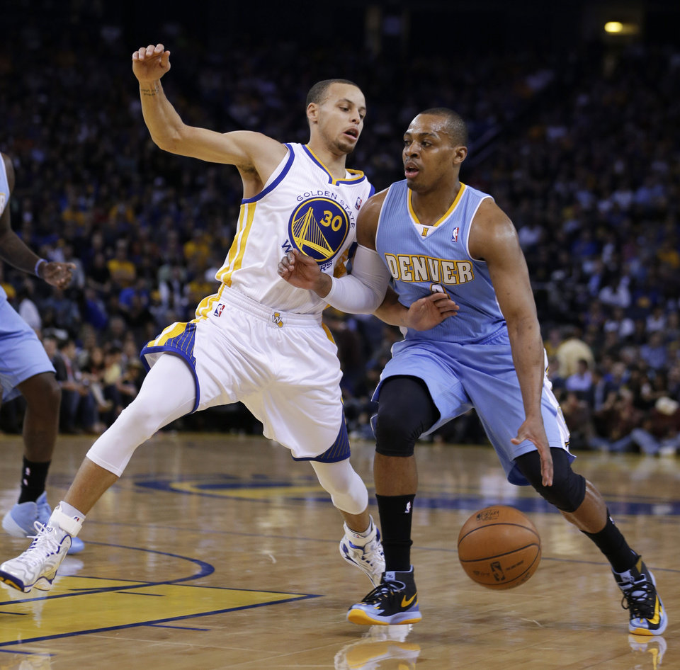 Photo - Denver Nuggets' Randy Foye, right, drives the ball against Golden State Warriors' Stephen Curry during the first half of an NBA basketball game Wednesday, Jan. 15, 2014, in Oakland, Calif. (AP Photo/Ben Margot)