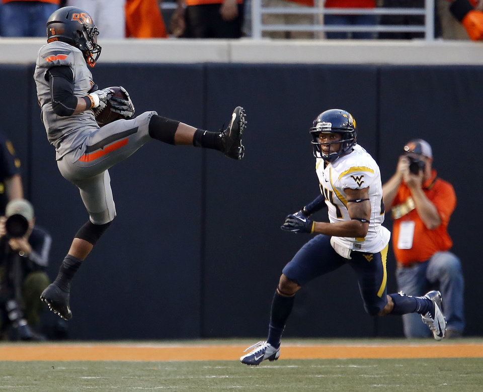 Photo - Oklahoma State's Josh Stewart (5) catches a pass in front of West Virginia's Cecil Level (24) in the third quarter during a college football game between Oklahoma State University (OSU) and the West Virginia University at Boone Pickens Stadium in Stillwater, Okla., Saturday, Nov. 10, 2012. Photo by Sarah Phipps, The Oklahoman