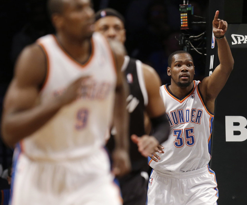 Oklahoma City Thunder's Kevin Durant points after scoring during the second half of an NBA basketball game against the Brooklyn Nets, Friday, Jan. 31, 2014, in New York. The Thunder defeated the Nets 120-95. (AP Photo/Seth Wenig)