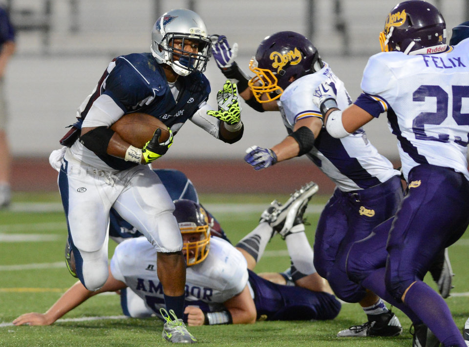 Photo - Freedom High's Joe Mixon (20) left, tries to get past the Amador Valley High defense before being tackled in the second quarter of their football game in Oakley, Calif., on Friday, Aug. 30, 2013. (Doug Duran/Bay Area News Group)