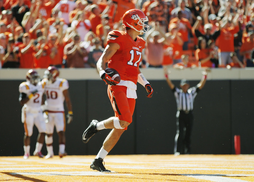 Photo - Oklahoma State's Charlie Moore (17) runs through the end zone after a touchdown catch in the second quarter during a college football game between Oklahoma State University (OSU) and Iowa State University (ISU) at Boone Pickens Stadium in Stillwater, Okla., Saturday, Oct. 20, 2012. Photo by Nate Billings, The Oklahoman