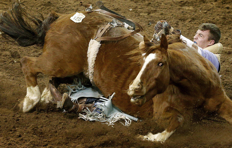 Cody Parker of Stilwell, Okla., gets caught under his horse during the bareback bronc competition during the International Finals Rodeo at Jim Norick Arena at State Fair Park in Oklahoma City, Saturday, Jan. 18, 20914. Parker held on as his horse rolled over on him and was able to stay on for the ride. Photo by Bryan Terry, The Oklahoman