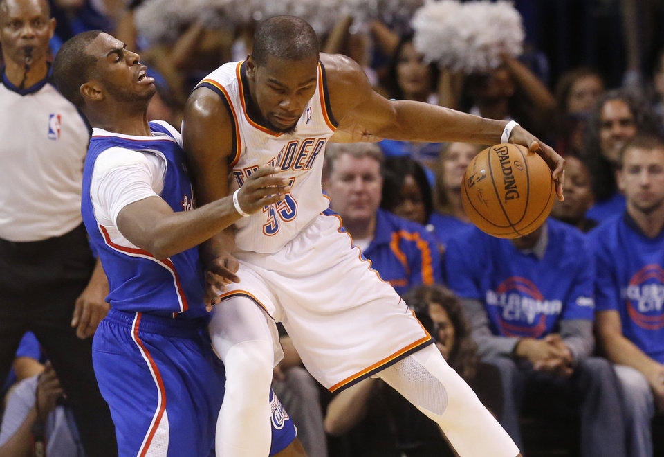 Photo - Oklahoma City Thunder forward Kevin Durant, right, drives against Los Angeles Clippers guard Chris Paul, left, in the second quarter of Game 1 of the Western Conference semifinal NBA basketball playoff series in Oklahoma City, Monday, May 5, 2014. (AP Photo/Sue Ogrocki)