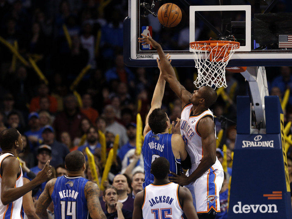 Photo - Oklahoma City's Serge Ibaka (9) blocks the shot of Nikola Vucevic (9) in the final seconds of during the NBA basketball game between the Oklahoma City Thunder and the Orlando Magic at the Chesapeake Energy Arena, Sunday, Dec. 15,  2013. Photo by Sarah Phipps, The Oklahoman