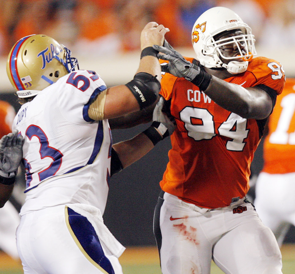 OSU's Anthony Rogers (94) gets away from Trent Dupy (53) of TU during the college football game between the University of Tulsa (TU) and Oklahoma State University (OSU) at Boone Pickens Stadium in Stillwater, Oklahoma, Saturday, September 18, 2010. OSU won, 65-28. Photo by Nate Billings, The Oklahoman ORG XMIT: KOD