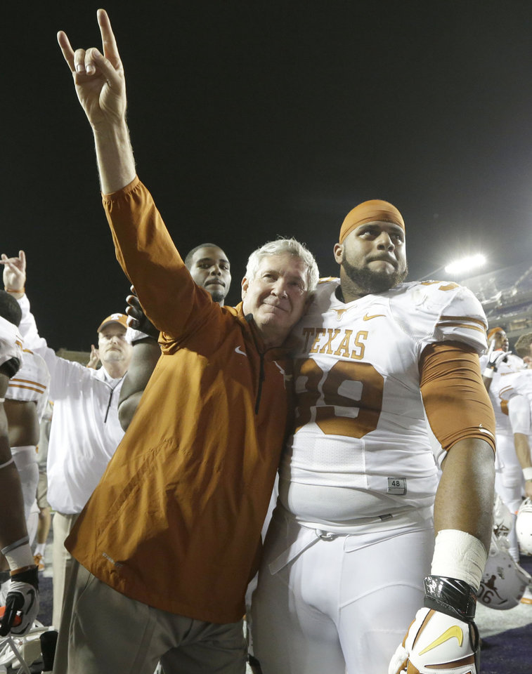 Texas head coach Mack Brown, left, hugs Texas defensive tackle Desmond Jackson (99) as he does the hook 'em horns sign  after their NCAA college football game against  TCU early Sunday morning, Oct. 27, 2013, in Fort Worth, Texas.  Texas won 30-7. (AP Photo/LM Otero)