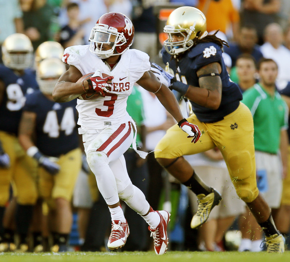 Photo - Oklahoma's Sterling Shepard (3) runs after a catch in front of Notre Dame's Ishaq Williams (11) on his way to a touchdown in the fourth quarter during a college football game between the University of Oklahoma Sooners and the Notre Dame Fighting Irish at Notre Dame Stadium in South Bend, Ind., Saturday, Sept. 28, 2013. OU won, 35-21. Photo by Nate Billings, The Oklahoman