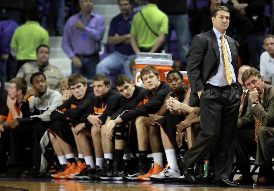 Oklahoma State coach Travis Ford and his bench watch the final moments of an NCAA college basketball game against Kansas State, Saturday, Jan. 5, 2013, in Manhattan, Kan. Kansas State won 73-67. (AP Photo/Charlie Riedel) ORG XMIT: KSCR113