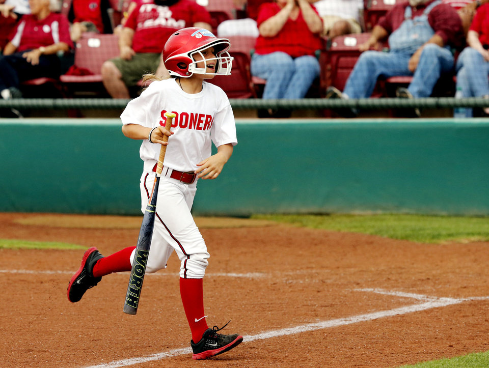 Photo - Casey Angle, sister of Moore tornado victim Sydney Angle performs as bat girl during the NCAA Super Regional softball game as the University of Oklahoma (OU) Sooners defeats Texas A&M 10-2 at Marita Hines Field on Friday, May 24, 2013 in Norman, Okla. Photo by Steve Sisney, The Oklahoman