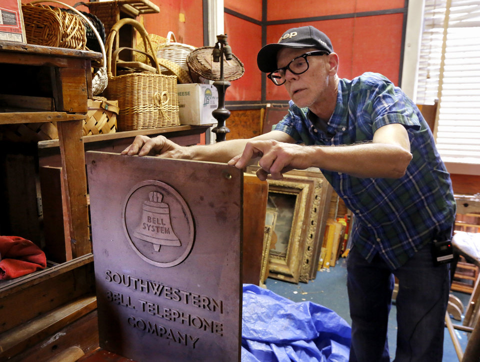 Photo -  Max Hester looks at an old bronze plaque that once graced a Southwestern Bell office. The plaque is among hundreds of items inside his parents' antique store May 28 in Choctaw. Photo by Jim Beckel, The Oklahoman   Jim Beckel -