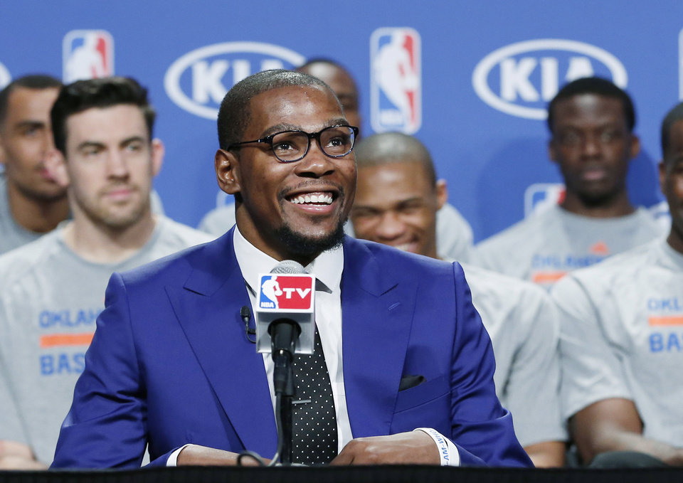 Photo - Oklahoma City Thunder's Kevin Durant, with his teammates seated behind him, smiles during the news conference to announce that Durant is the winner of the 2013-14 Kia NBA Basketball Most Value Player Award in Oklahoma City, Tuesday, May 6, 2014. (AP Photo/Sue Ogrocki)