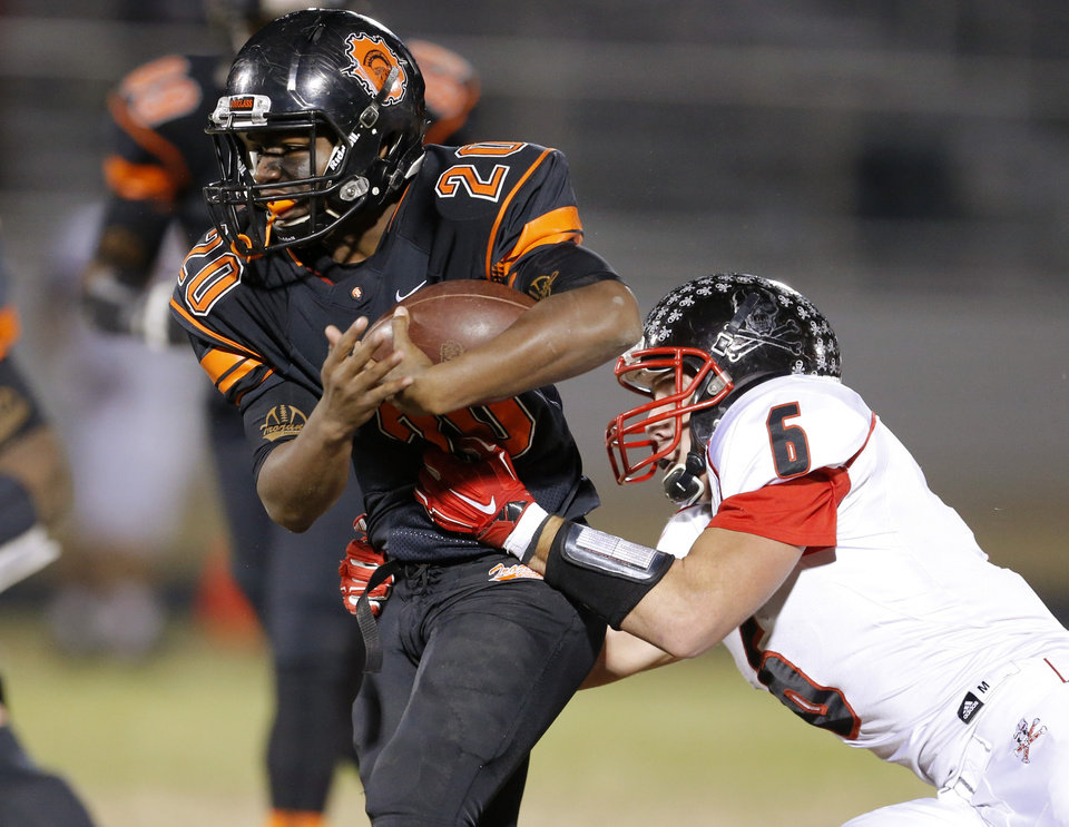 Photo - Douglass' Chris Friday trie to get past Locust Grove's Jason Pirtle during their high school football playoff game at Douglass in Oklahoma City, Friday, Nov. 28, 2014. Photo by Bryan Terry, The Oklahoman