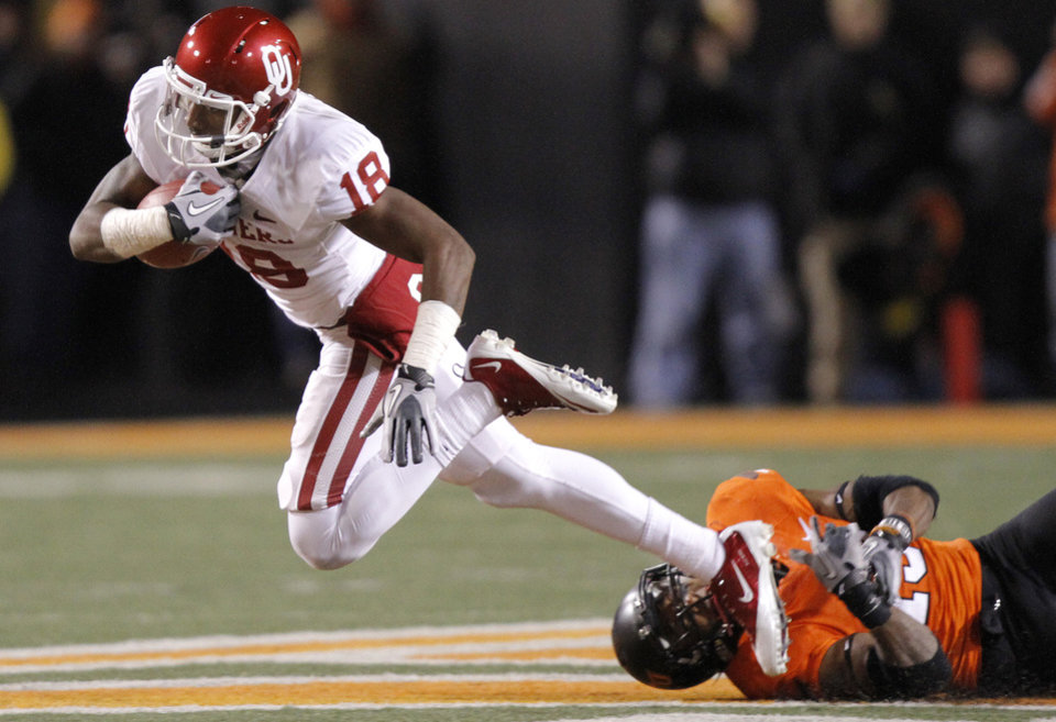 Oklahoma\'s Kameel Jackson (18) is tripped up by Oklahoma State\'s Brodrick Brown (19) during the Bedlam college football game between the Oklahoma State University Cowboys (OSU) and the University of Oklahoma Sooners (OU) at Boone Pickens Stadium in Stillwater, Okla., Saturday, Dec. 3, 2011. Photo by Chris Landsberger, The Oklahoman