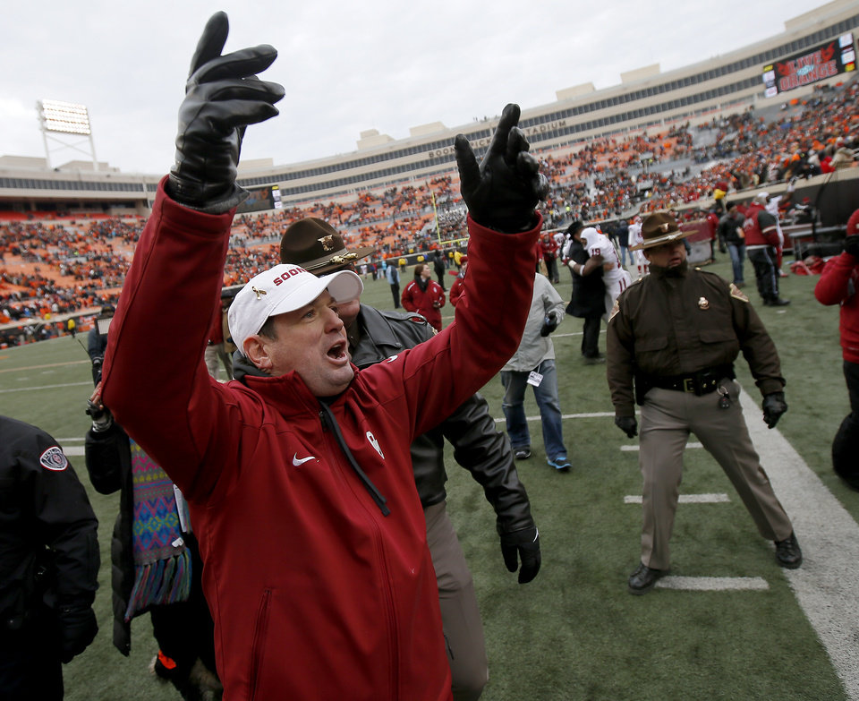 Photo - Oklahoma coach Bob Stoops celebrates towards the OU crowd after the Bedlam college football game between the Oklahoma State University Cowboys (OSU) and the University of Oklahoma Sooners (OU) at Boone Pickens Stadium in Stillwater, Okla., Saturday, Dec. 7, 2013. Oklahoma won 33-24. Photo by Bryan Terry, The Oklahoman
