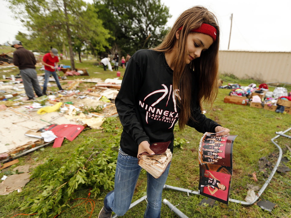 Photo - McKenzee Sneed, 14, recovers a team photo and bible as friends and family of her parents Kris and Christeen Allen look for mementos and valuables in the wreckage of their mobil home destroyed by storms on Friday, April 29, 2016 in Ninnekah, Okla.  Photo by Steve Sisney, The Oklahoman