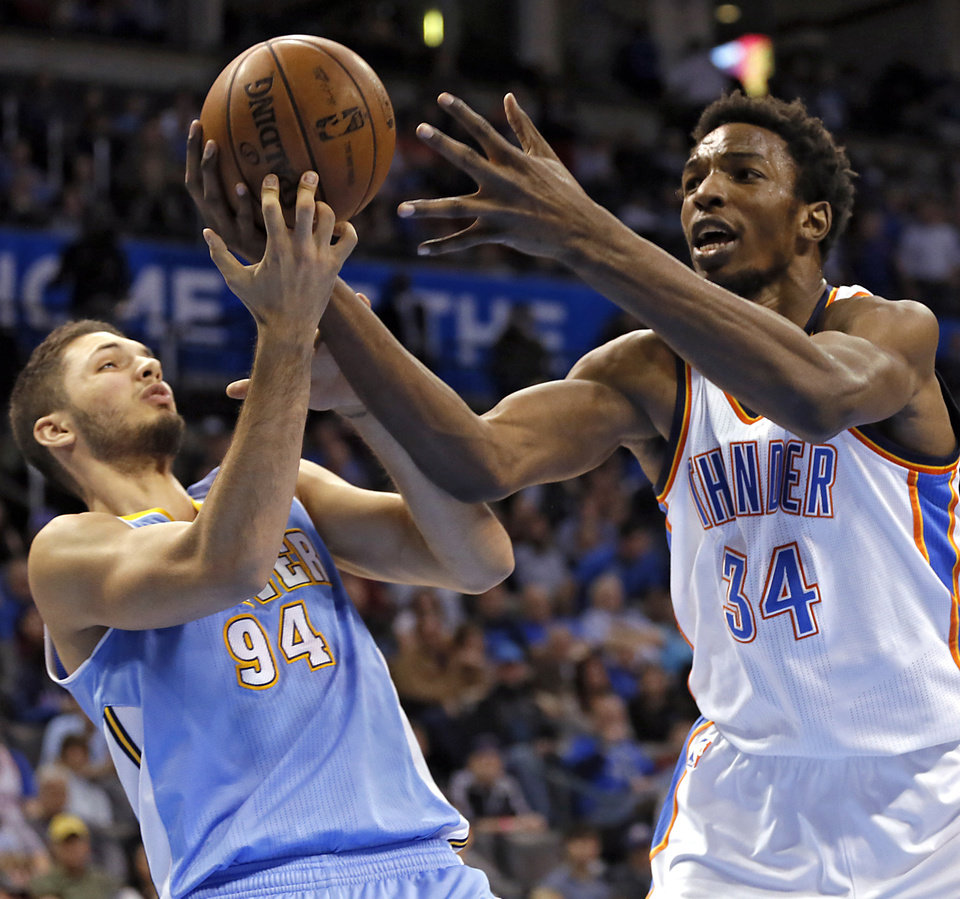 Oklahoma City\'s Hasheem Thabeet (34) battles for the ball with Denver\'s Evan Fournier (94) during the NBA basketball game between the Oklahoma City Thunder and the Denver Nuggets at the Chesapeake Energy Arena on Wednesday, Jan. 16, 2013, in Oklahoma City, Okla. Photo by Chris Landsberger, The Oklahoman