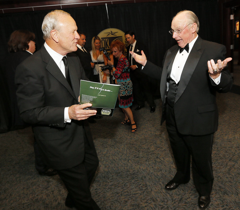 Photo - Barry Switzer, left, makes fun of the picture of inductee Pat Jones on the program for the 2012 Oklahoma Sports Hall of Fame induction ceremony at a gathering at the Oklahoma Sports Hall of Fame before the ceremony in Oklahoma City, Monday, Aug. 6, 2012. Switzer gave Jones' introduction at the ceremony. Photo by Nate Billings, The Oklahoman