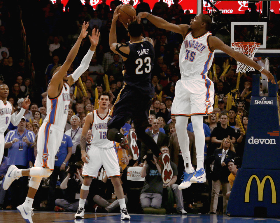 Photo - New Orleans' Anthony Davis (23) shoots the game-winning basket over Oklahoma City's Kevin Durant (35) and Andre Roberson (21) during an NBA game between the Oklahoma City Thunder and the New Orleans Pelicans at Chesapeake Energy Arena on Friday, Feb. 6, 2015. Photo by Bryan Terry, The Oklahoman