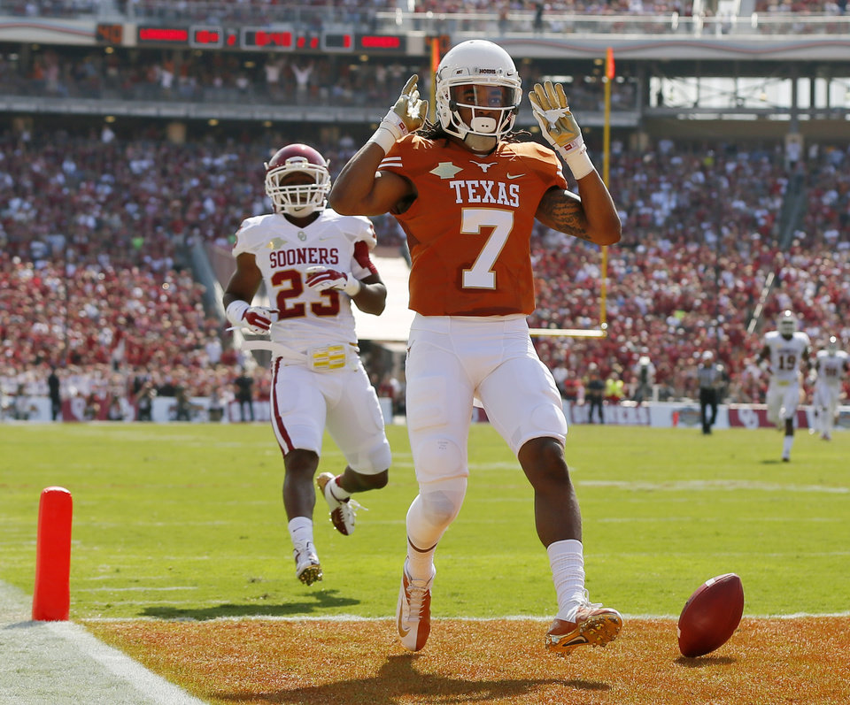Photo - UT's Marcus Johnson (7) celebrates a touchdown in front of OU's Kass Everett (23) in the second quarter during the Red River Rivalry college football game between the University of Oklahoma Sooners and the University of Texas Longhorns at the Cotton Bowl Stadium in Dallas, Saturday, Oct. 12, 2013. Photo by Nate Billings, The Oklahoman