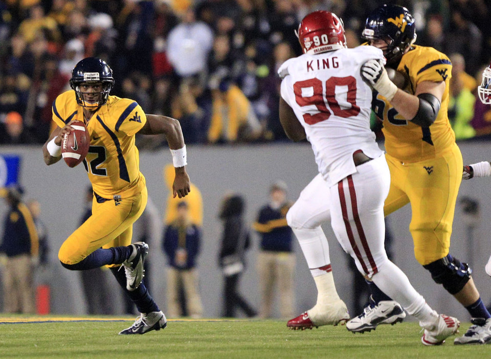 Photo - West Virginia quarterback Geno Smith (12) carries the ball as Curtis Feigt (62) blocks Oklahoma's David King (90) during the fourth quarter of their NCAA college football game against Oklahoma in Morgantown, W.Va., on Saturday, Nov. 17, 2012. Oklahoma won 50-49. (AP Photo/Christopher Jackson)