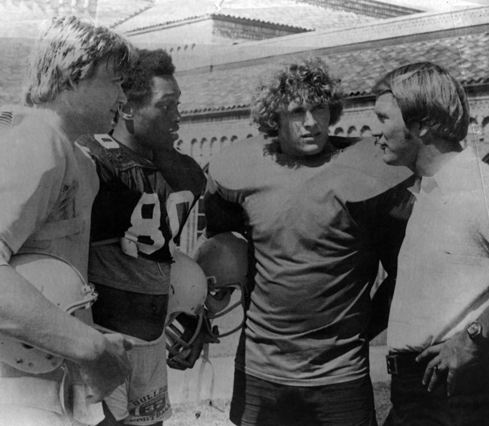 "FOOTBALL OU UNIVERSITY OF OKLAHOMA BARRY SWITZER B 1977 27.jpg: Caption reads ""University of Oklahoma coach Barry Switzer, far right, talks to three OU recruits at Oil Bowl workouts Wednesday. From left, they are Keith Wilson, Putnam West; Byron Paul, Altus; and John Higginbothan, Hugo."" Photographer unknown. Date photo was taken unknown. Photo published in The Daily Oklahoman 8-4-1977."