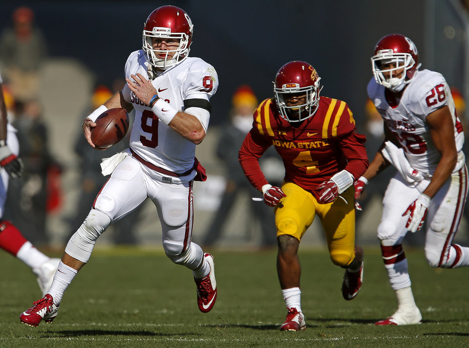 Photo - Oklahoma's Trevor Knight (9) runs past Iowa State's Sam E. Richardson (4) during a college football game between the University of Oklahoma Sooners (OU) and the Iowa State Cyclones (ISU) at Jack Trice Stadium in Ames, Iowa, Saturday, Nov. 1, 2014. Photo by Bryan Terry, The Oklahoman