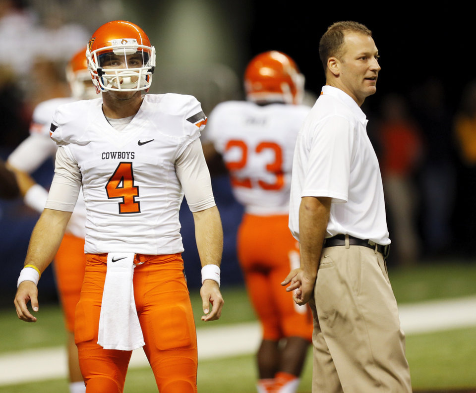 OSU offensive coordinator Mike Yurcich stands near quarterback J.W. Walsh (4) as the Cowboys warm up before a college football game between the University of Texas at San Antonio Roadrunners (UTSA) and the Oklahoma State University Cowboys (OSU) at the Alamodome in San Antonio, Saturday, Sept. 7, 2013.  Photo by Nate Billings, The Oklahoman