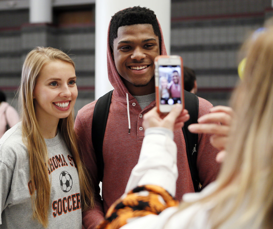 Photo - OSU soccer signee Lana Duke has her picture taken with Caleb McCain, an Edmond Memorial basketball player, during signing day for student athletes at Edmond Memorial High School in Edmond, Okla., Wednesday, Feb. 5, 2014. Photo by Nate Billings, The Oklahoman