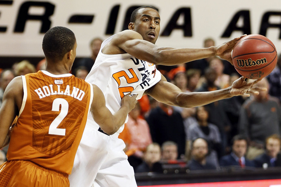 Photo - Oklahoma State's Markel Brown (22) passes away from Texas' Demarcus Holland (2) during a men's college basketball game between Oklahoma State University (OSU) and the University of Texas at Gallagher-Iba Arena in Stillwater, Okla., Saturday, March 2, 2013. Photo by Nate Billings, The Oklahoman
