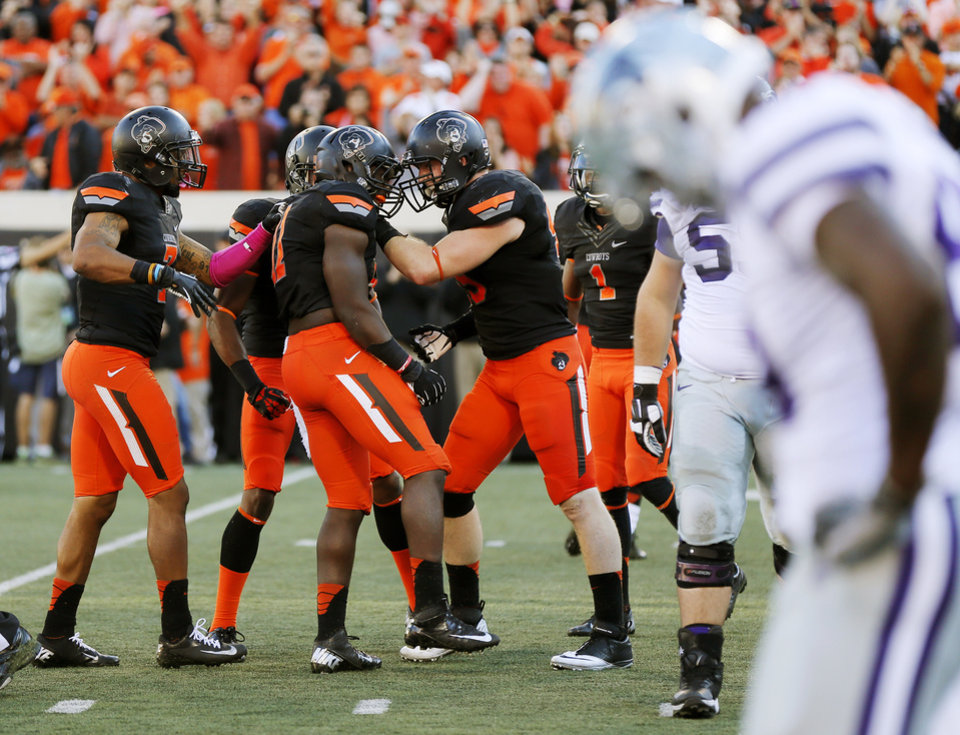 The OSU Cowboys celebrate an interception in the fourth quarter by Shaun Lewis (11), middle, during a college football game between the Oklahoma State University Cowboys (OSU) and the Kansas State University Wildcats (KSU) at Boone Pickens Stadium in Stillwater, Okla., Saturday, Oct. 5, 2013. OSU won, 33-29. Photo by Nate Billings, The Oklahoman