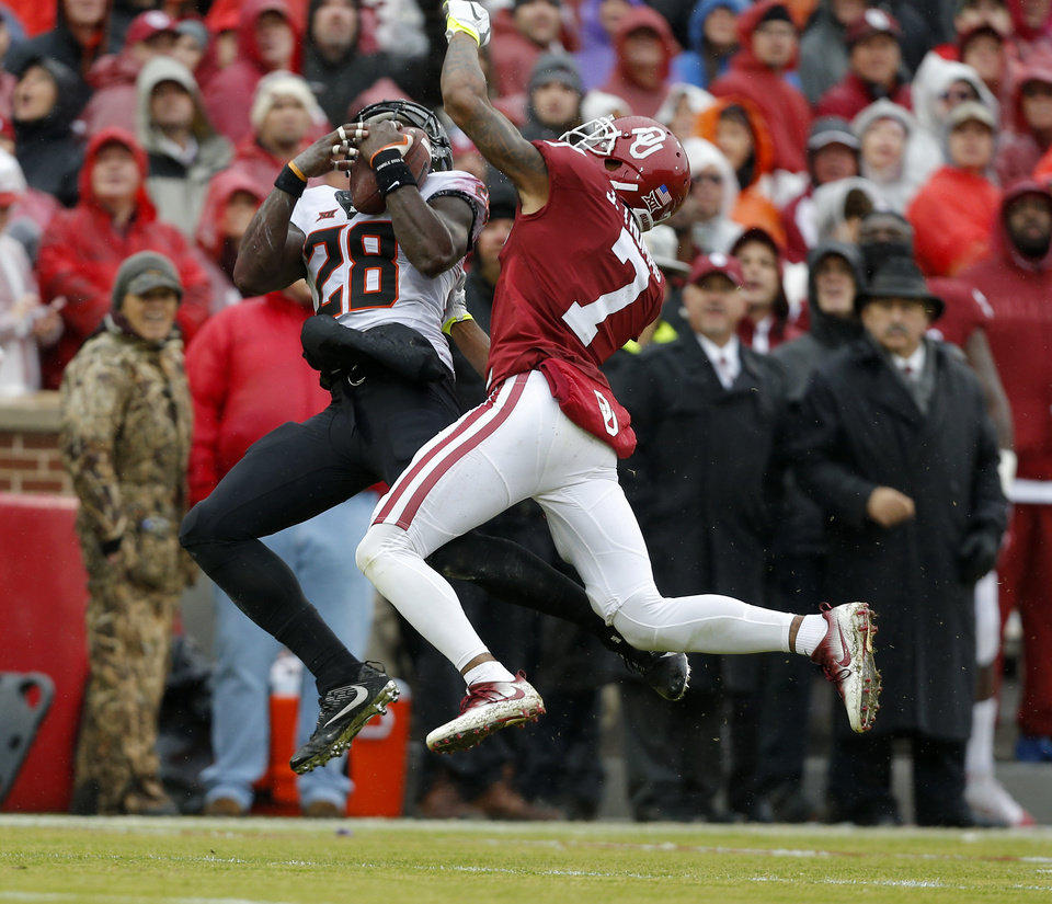 Photo - Oklahoma State's James Washington (28) makes a catch as Oklahoma's Jordan Thomas (7) defends in the second quarter during the Bedlam college football game between the Oklahoma Sooners (OU) and the Oklahoma State Cowboys (OSU) at Gaylord Family - Oklahoma Memorial Stadium in Norman, Okla., Saturday, Dec. 3, 2016. OU won 38-20. Photo by Sarah Phipps, The Oklahoman