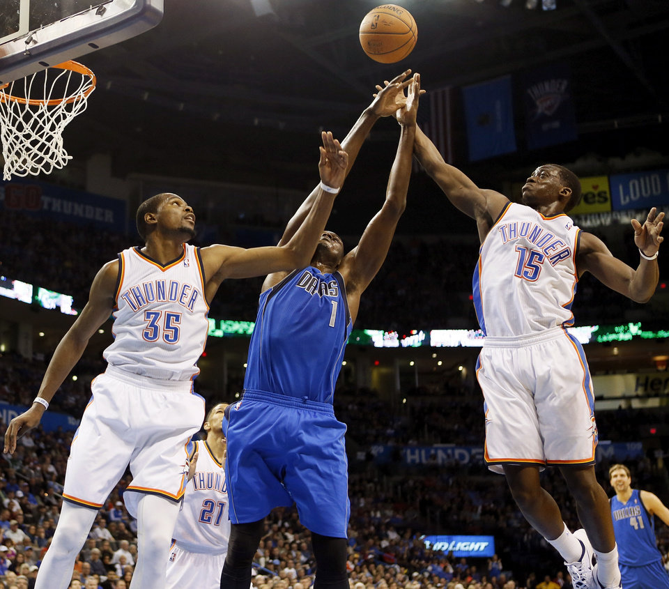 Photo - From left, Oklahoma City's Kevin Durant (35), Dallas' Samuel Dalembert (1) and Oklahoma City's Reggie Jackson (15) try to rebound the ball during an NBA basketball game between the Oklahoma City Thunder and the Dallas Mavericks at Chesapeake Energy Arena in Oklahoma City, Sunday, March 16, 2014. Dallas won, 109-86. Photo by Nate Billings, The Oklahoman
