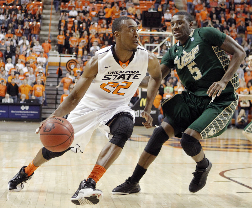 Photo - Oklahoma State 's Markel Brown (22) drives past South Florida Bulls' Jawanza Poland (5) during the college basketball game between Oklahoma State University (OSU) and the University of South Florida (USF) on Wednesday , Dec. 5, 2012, in Stillwater, Okla.   Photo by Chris Landsberger, The Oklahoman