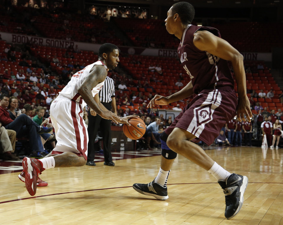 Oklahoma's Cameron Clark (21) drives the ball past UALR's Mareik Isom (21) during a mens basketball game between OU and UALR at Lloyd Noble Center in Norman, Okla., Friday, Nov. 29, 2013.  Photo by Garett Fisbeck, For The Oklahoman