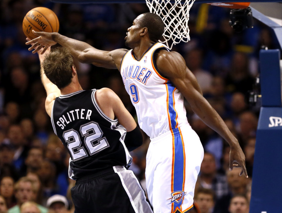 Oklahoma City's Serge Ibaka defends a shot by San Antonio's Tiago Splitter during an NBA basketball game between the Oklahoma City Thunder and the San Antonio Spurs at Chesapeake Energy Arena in Oklahoma City, Wednesday, Nov. 27, 2013. Photo by Nate Billings, The Oklahoman