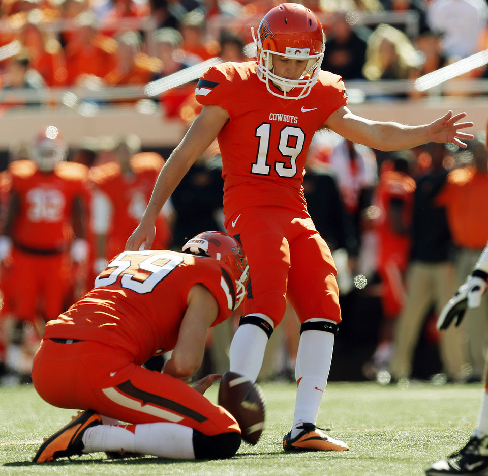 Oklahoma State\'s Ben Grogan (19) kicks a field goal as Oklahoma State\'s Michael Reichenstein (59) holds in the second quarter during a college football game between the Oklahoma State University Cowboys (OSU) and the Texas Christian University Horned Frogs (TCU) at Boone Pickens Stadium in Stillwater, Okla., Saturday, Oct. 19, 2013. Photo by Nate Billings, The Oklahoman