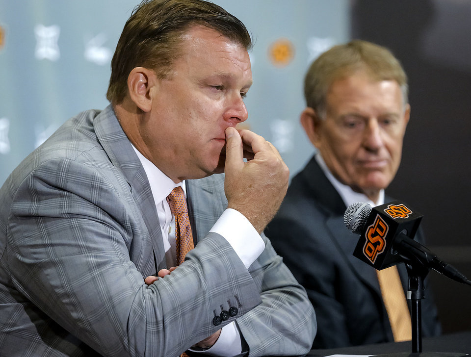 Photo -  Oklahoma State University athletic director Mike Holder, right, looks on as OSU men's basketball coach Brad Underwood speaks Friday during a news conference about the death of player Tyrek Coger. [Photo by Chris Landsberger, The Oklahoman]