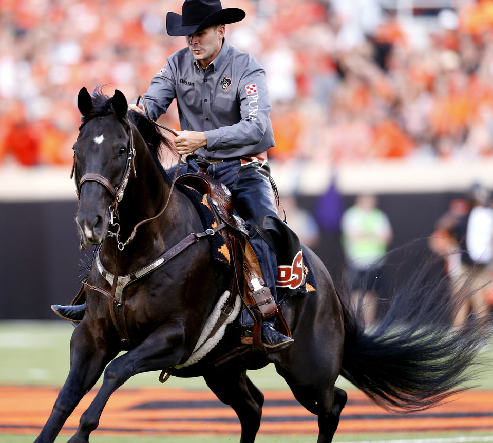Photo - Bullet is hard to handle after a score  during the college football game between the Oklahoma State Cowboys (OSU) and the Central Arkansas Bears at Boone Pickens Stadium in Stillwater, Okla., Saturday, Sept. 12, 2015. The iconic horse bucked off the rider during the pre-game festivities.  Photo by Steve Sisney, The Oklahoman