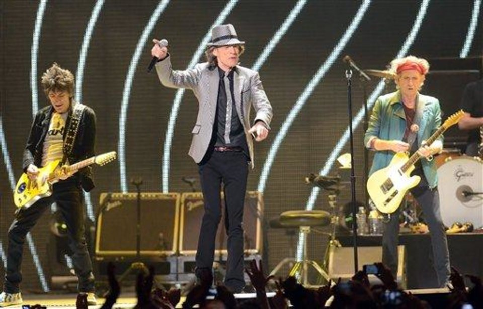 In this Saturday, Dec. 15, 2012 file photo, singer Mick Jagger, center, guitarists Ronnie Wood, left, and Keith Richards, of The Rolling Stones perform live at the Prudential Center in Newark, N.J. (Photo by Evan Agostini/Invision/AP, File)
